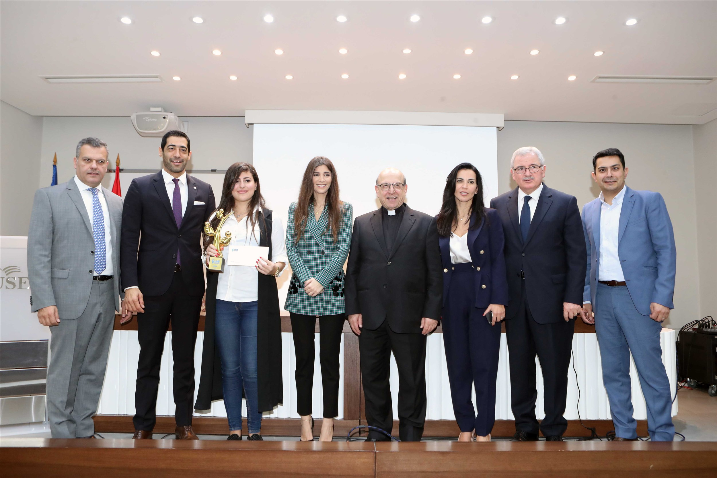 the winner of the holy spitiy univesity of kaslik sarah abi abdallah shares the stage with the jury and mrs. inas al jarmakani in order to receive her prize and trophy, because she dared to dream!
