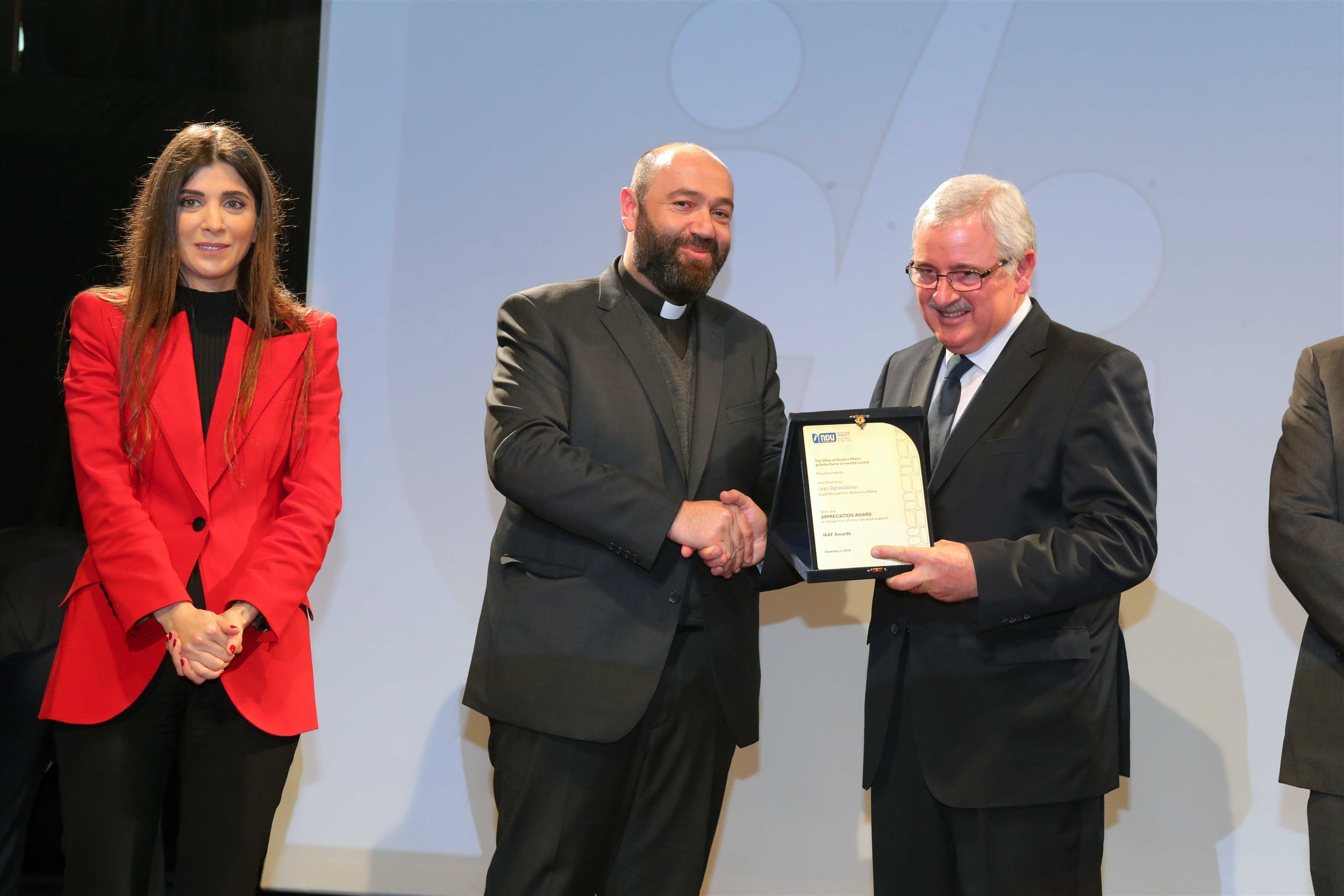 minister of state for women affairs mr. jean oghassapian receives a sheild of appreciation from the notre dame university- louaize for his accomplishments.