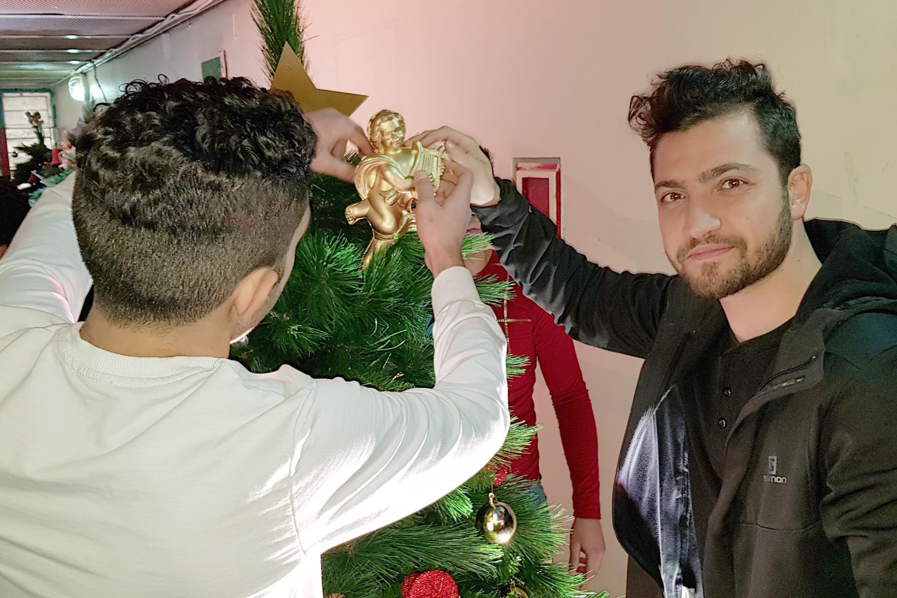 actor elias al zayek helping in the decoration of the christmas tree.