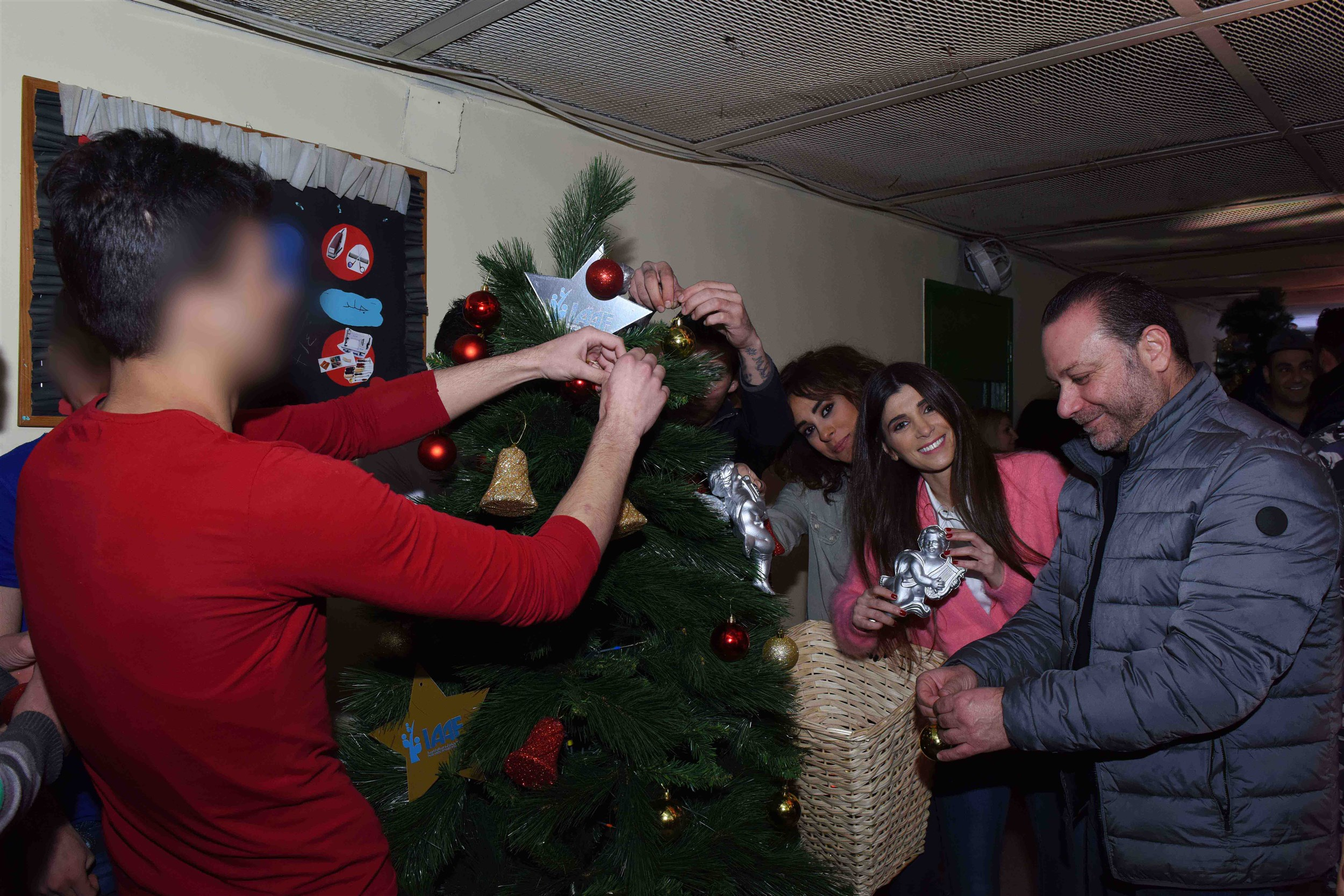 news anchor bassam abou zeid, actress andree nacouzi and mrs. inas al jarmakani decorating a christmas tree with the juvenile prisoners.