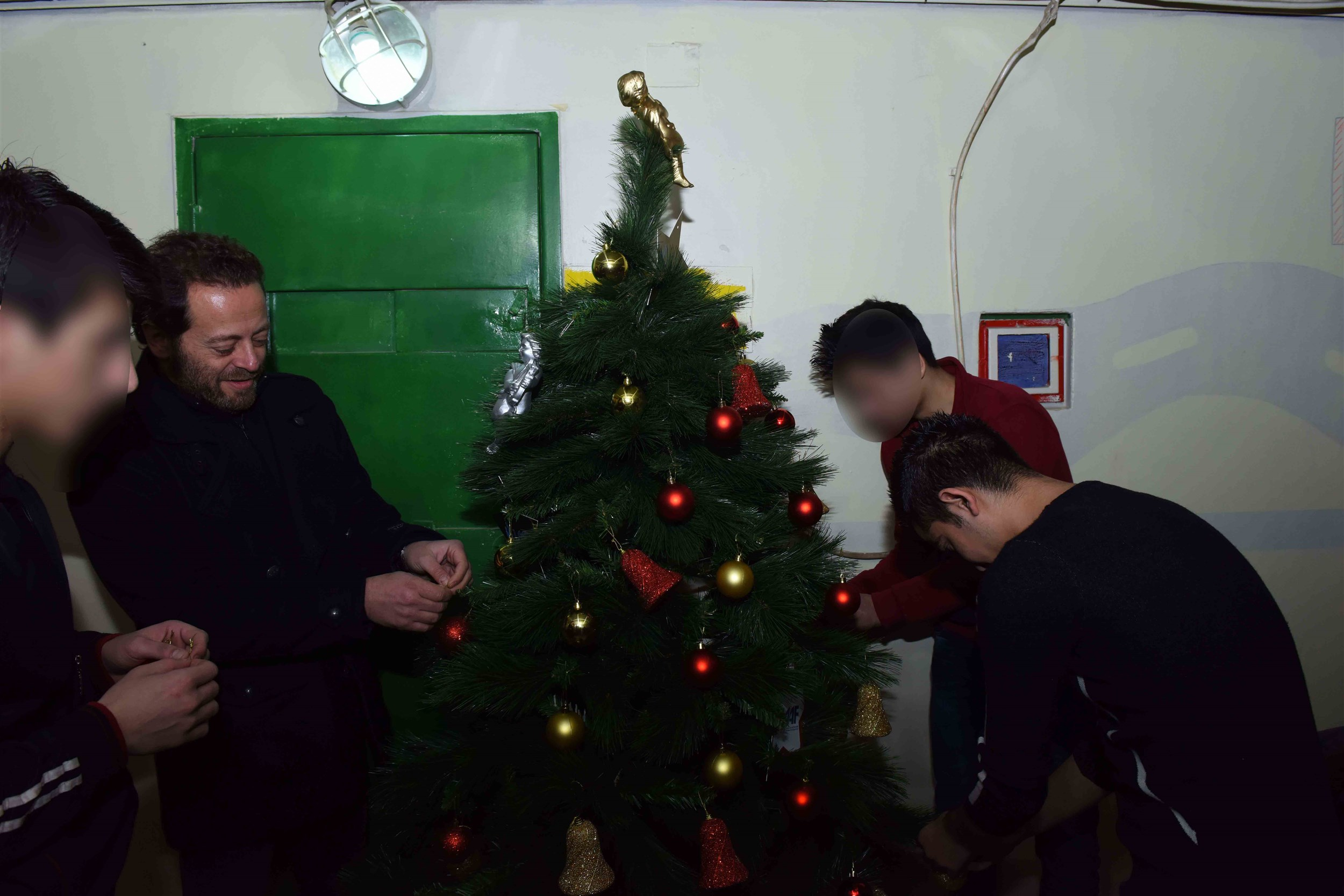 actor badih abou chakra helping in the decoration of the christmas tree.