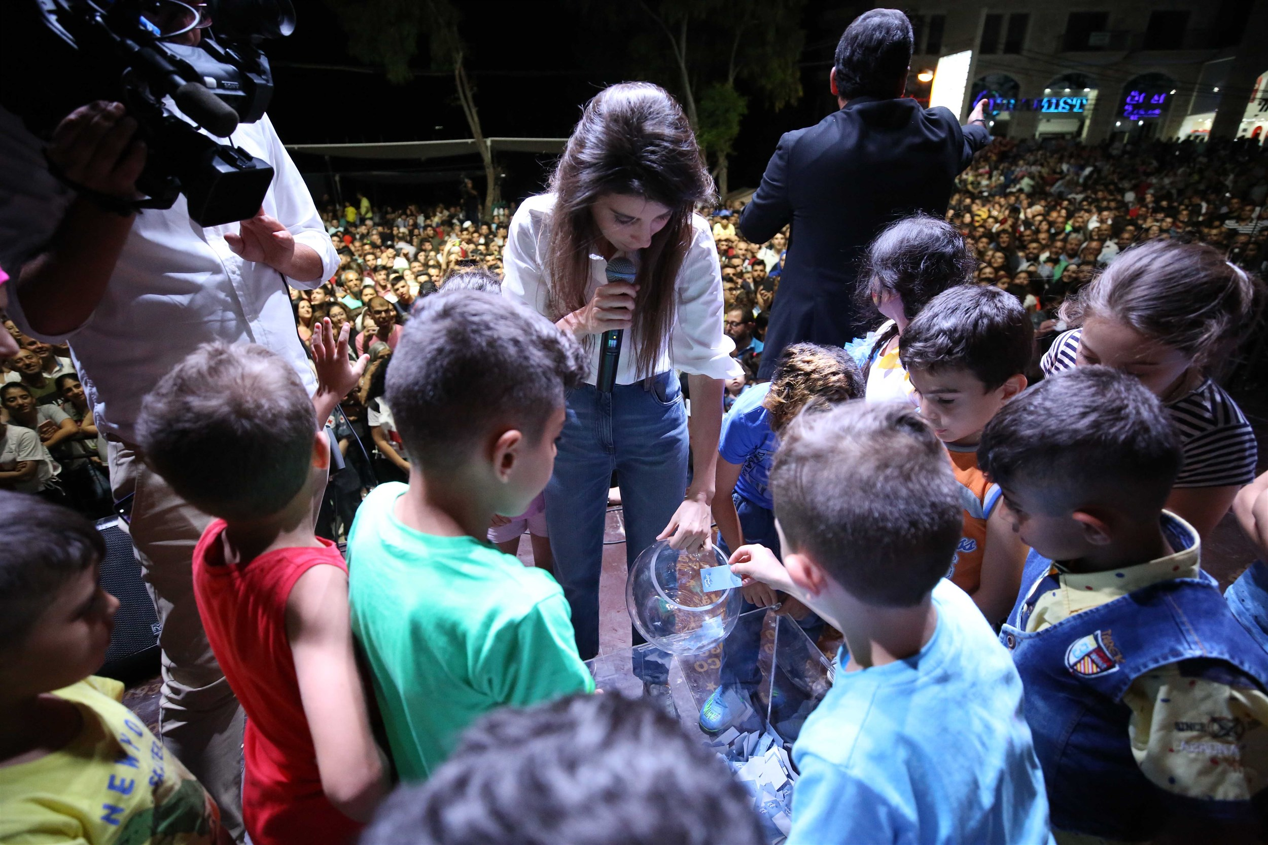 mrs. inas al jarmakani and the children draw the name of the winning family for the car gifted by the iaaf.