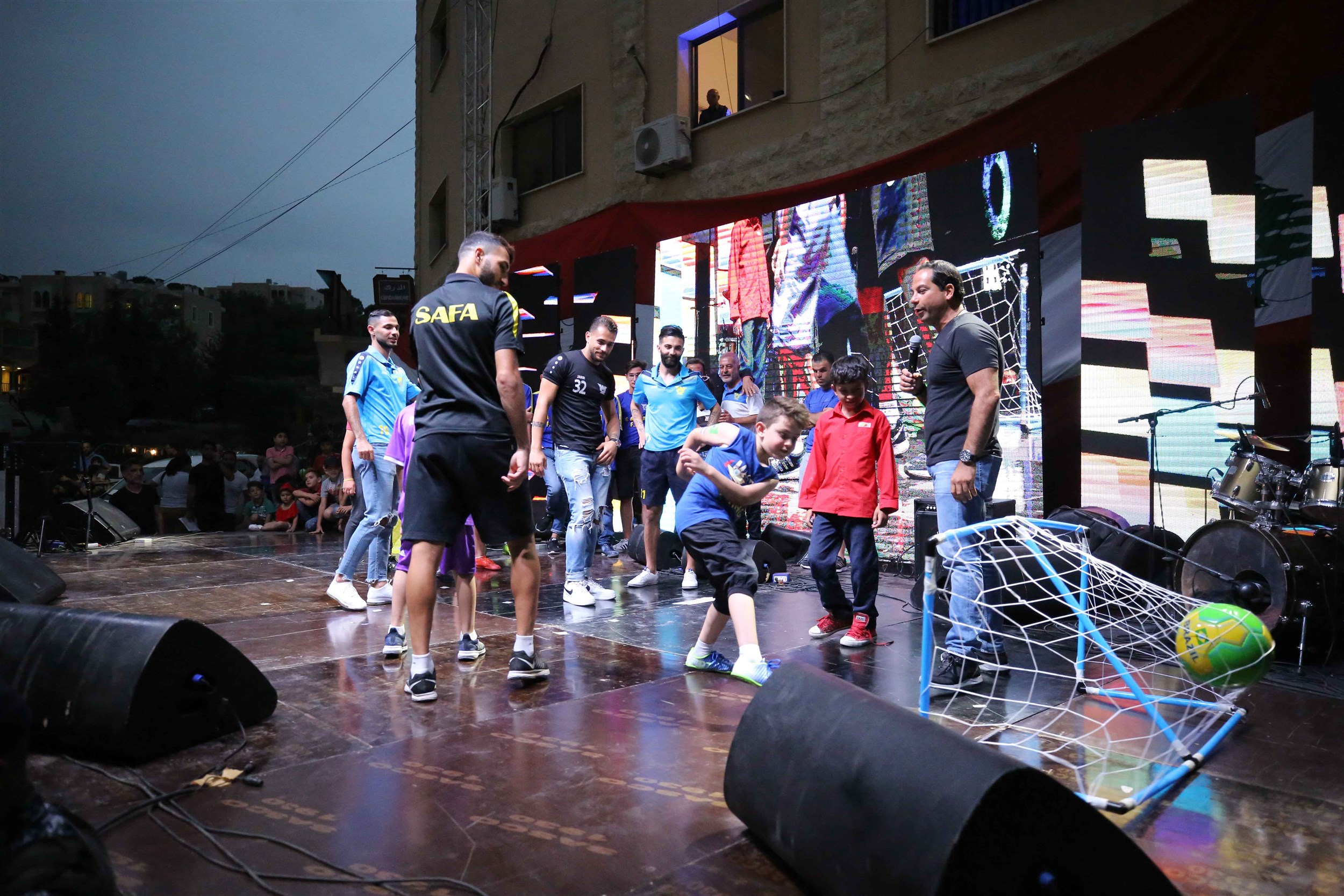 """the football team """"safa"""" and host michel azzi enjoying a friendly game with the audience."""
