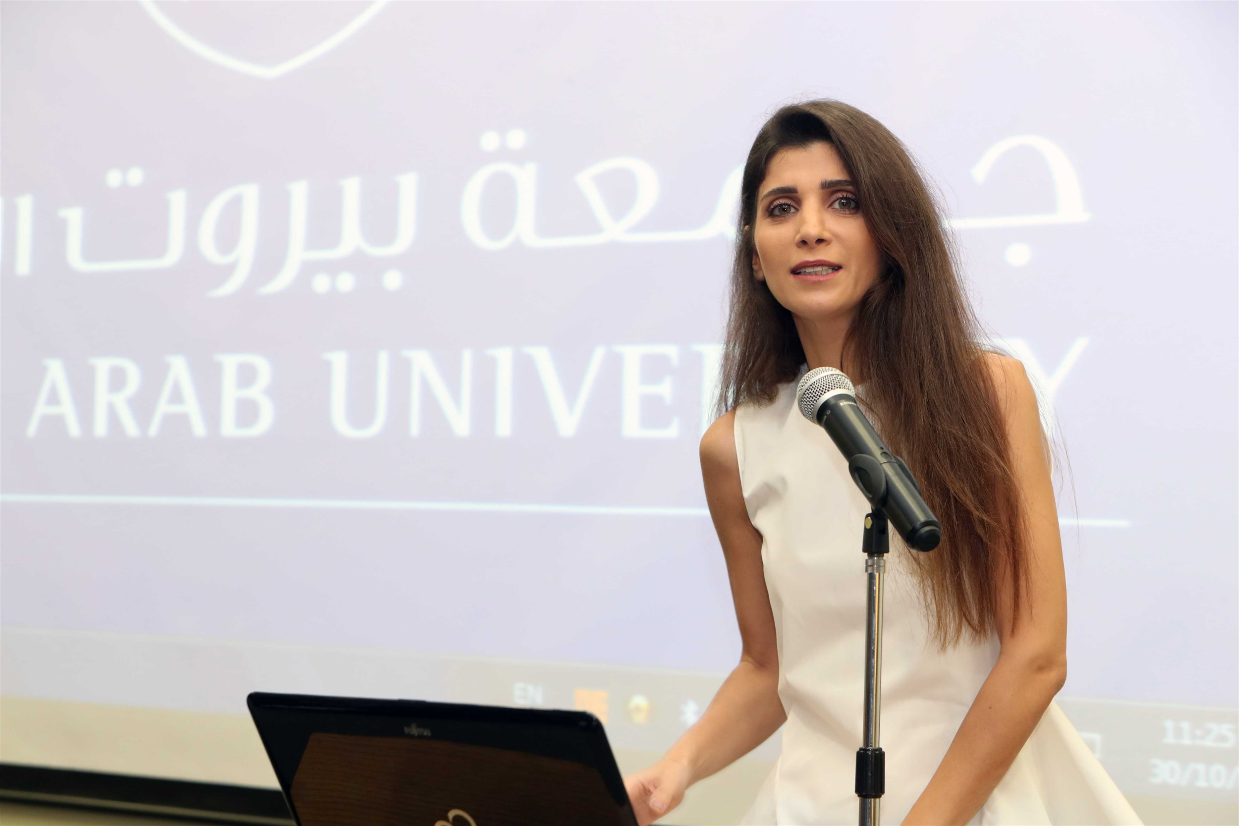 mrs. inas al jarmakani delivering her speech about her on-going belief in making dreams come true and defending the ability of imagination and sticking to one's dream and passion.